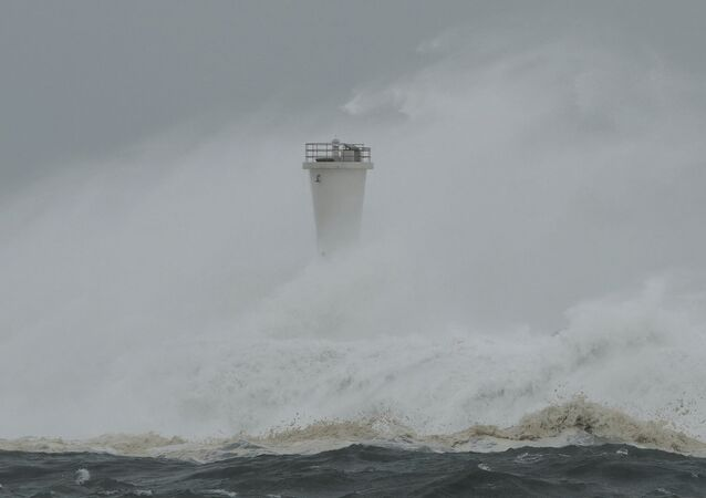 Surging waves hit against the breakwater and a lighthouse as Typhoon Hagibis approaches at a port in the town of Kiho, Mie prefecture, central Japan.