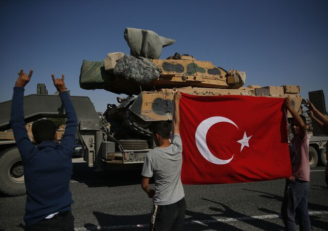 Local residents applaud as a convoy of Turkish forces trucks transporting tanks is driven in Sanliurfa province, southeastern Turkey, at the border with Syria