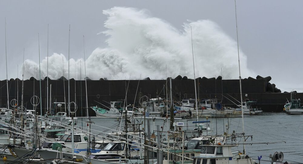 Surging waves hit against the breakwater behind fishing boats as Typhoon Hagibis approaches at a port in town of Kiho, Mie prefecture, central Japan Saturday
