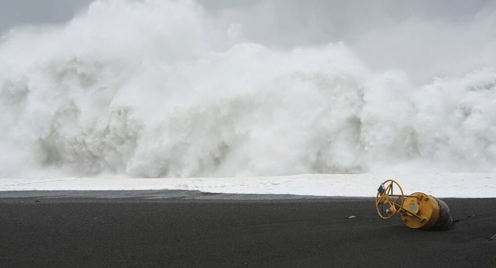 A buoy lies on a beach is seen in front of surging waves as Typhoon Hagibis approaches in Kumano, Mie prefecture, central Japan Saturday