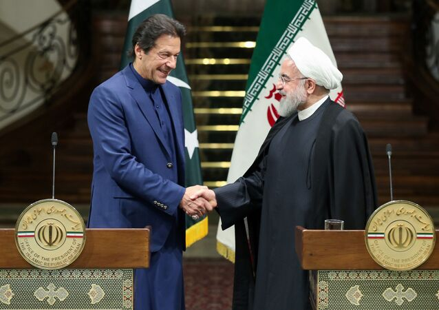 Iranian President Hassan Rouhani shakes hands with Pakistani Prime Minister Imran Khan during a news conference in Tehran, Iran, October 13, 2019