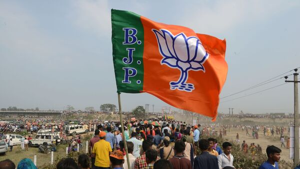 Indian supporters of the Bharatiya Janata Party (BJP) carry a party flag on their way to attend a campaign rally while wearing masks of Indian Prime Minister Narendra Modi ahead of the national elections in Siliguri, 3 April 2019 - Sputnik International