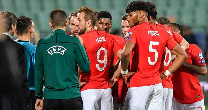 England's captain Harry Kane (centre) speaks with the referee after the match with Bulgaria was interrupted by racist chanting