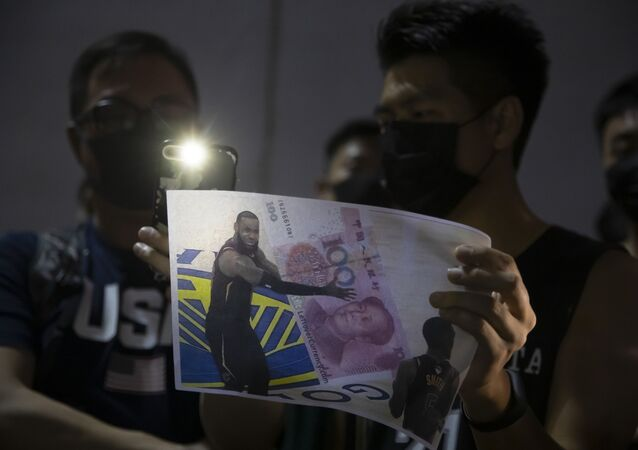 A demonstrator holds a sign showing Lebron James embracing a Chinese 100-yuan banknote during a rally at the Southorn Playground in Hong Kong, Tuesday, Oct. 15, 2019