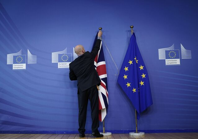 An official hangs a Union Jack next to an European Union flag at EU Headquarters in Brussels on 17 October 2019, ahead of a European Union Summit on Brexit.