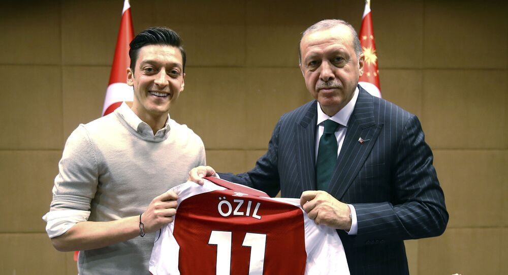In this file photo taken on Sunday, May 13, 2018, Turkey's President Recep Tayyip Erdogan, right, poses for a photo with Arsenal soccer player Mesut Ozil in London.
