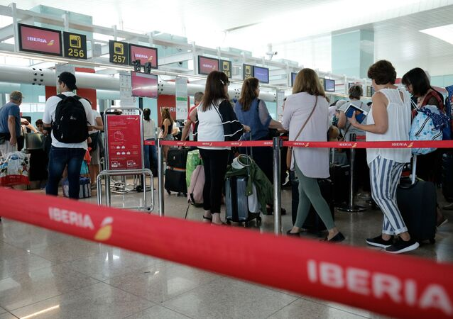Passengers queue in front of check-in counters of Spanish airline Iberia at Barcelona's 'El Prat' airport on July 27, 2019