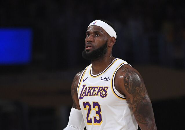 Los Angeles Lakers forward LeBron James looks on during the first half of a preseason NBA basketball game against the Golden State Warriors Wednesday, Oct. 16, 2019, in Los Angeles