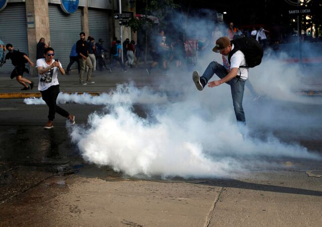A demonstrator kicks a tear gas canister during a protest against the increase in the subway ticket prices in Santiago, Chile, 18 October