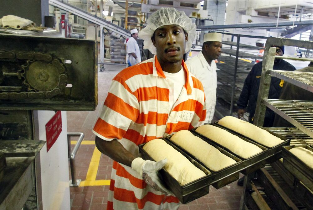 Inmate Nikos Alexis loads fresh dough into an oven at the Rikers Island jail bakery. He was part of a team of 20 inmates who earned some money baking thousands loaves of bread to feed a huge number of prisoners – in 2011 there were about 13,000 men and women behind bars.