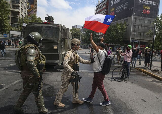 Army soldiers stop a man protesting with a Chilean flag, after a night of riots that forced President Sebastian Pinera to announce a state of emergency, in Santiago, Chile, Saturday, Oct. 19, 2019. The protests started on Friday afternoon when high school students flooded subway stations, jumping turnstiles, dodging fares and vandalizing stations as part of protests against a fare hike, but by nightfall had extended throughout Santiago with students setting up barricades and fires at the entrances to subway stations. (AP Photo/Esteban Felix)
