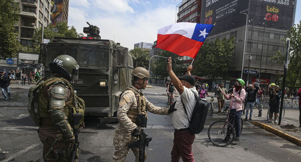 Army soldiers stop a man protesting with a Chilean flag, after a night of riots that forced President Sebastian Pinera to announce a state of emergency, in Santiago, 19 October 2019.  The protests started when high school students flooded subway stations, jumping turnstiles, dodging fares and vandalising stations as part of protests against a fare hike, but by nightfall had extended throughout Santiago with students setting up barricades and fires at the entrances to subway stations. (AP Photo/Esteban Felix)