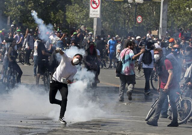 A protester returns a tear gas canister to police during clashes in Santiago, Chile, Sunday, 20 October 2019. Protests in the country have spilled over into a new day, even after President Sebastian Pinera cancelled the subway fare hike that prompted massive and violent demonstrations. (AP Photo/Esteban Felix)