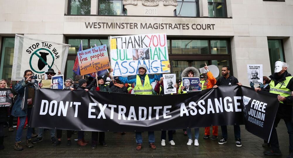 Demonstrators hold banners during a protest outside of Westminster Magistrates Court, where a case management hearing in the U.S. extradition case of WikiLeaks founder Julian Assange is held, in London, Britain, October 21, 2019