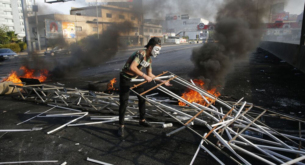 An anti-government protester adds to a makeshift barricade blocking a highway that links to north Lebanon in east Beirut, Lebanon, Sunday, Oct. 20, 2019