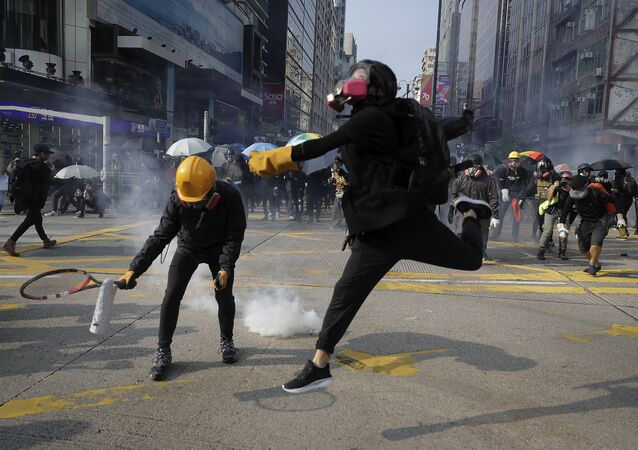 Protesters throw away the tear gas canisters fired by riot policemen during a rally in Hong Kong, Sunday, Oct. 20, 2019