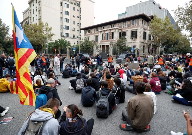 Supporters of Catalonia's independence sit on a street as they attend a protests over the jailing of Catalan separatist leaders outside Spanish Government offices in Barcelona, Spain, October 21, 2019