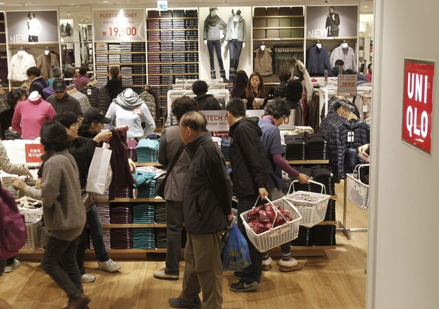 Customers shop at the newly opened Uniqlo flagship store at Myeongdong, one of the main shopping districts, in Seoul, South Korea, Friday, Nov. 11, 2011