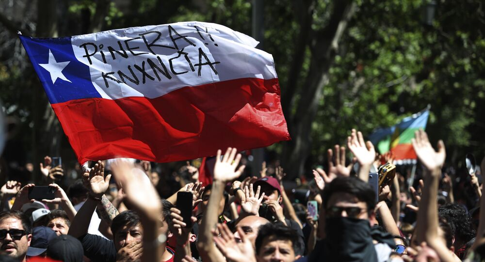 Protesters wave a Chilean flag, marked with a message that reads in Spanish: Pinera quit during a demonstration in Santiago, Chile, Monday, Oct. 21, 2019.