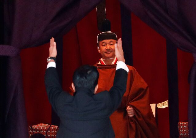 """Japan's Prime Minister Shinzo Abe raises his hands as he shouts """"banzai"""" or cheers in front of Emperor Naruhito during a ceremony to proclaim Emperor Naruhito's enthronement to the world, called Sokuirei-Seiden-no-gi, at the Imperial Palace in Tokyo, Japan October 22, 2019"""