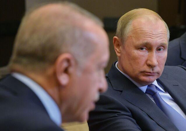 Russian President Vladimir Putin listens to his Turkish counterpart Recep Tayyip Erdogan during their meeting in the Black Sea resort of Sochi, Russia