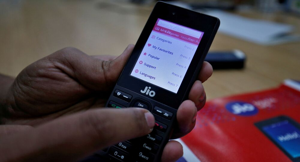 A sales person displays features of JioPhone as he poses for a photograph at a store of Reliance Industries' Jio telecoms unit, on the outskirts of Ahmedabad, India, September 26, 2017