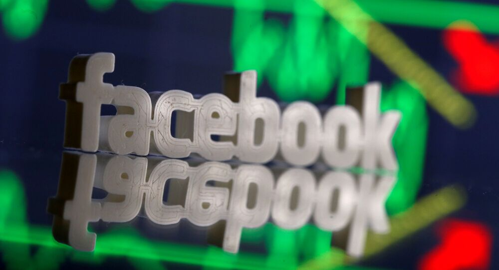 A 3D-printed Facebook logo is seen in front of displayed stock graph in this illustration photo, March 20, 2018