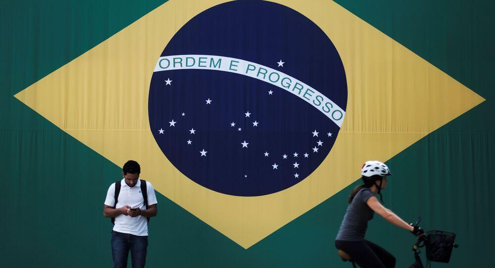 A man checks his mobile phone as a woman riding a bike passes next to a big Brazilian flag in Sao Paulo, Brazil June 28, 2018