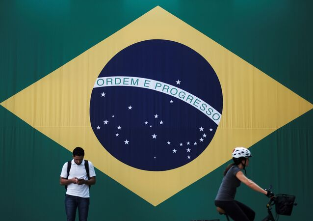 A man checks his mobile phone as a woman riding a bike passes next to a big Brazilian flag in Sao Paulo, Brazil June 28, 2018