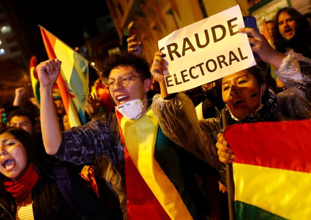 A protestor holds a banner reading Electoral Fraud as she takes part in a march in La Paz, Bolivia, October 25, 2019.