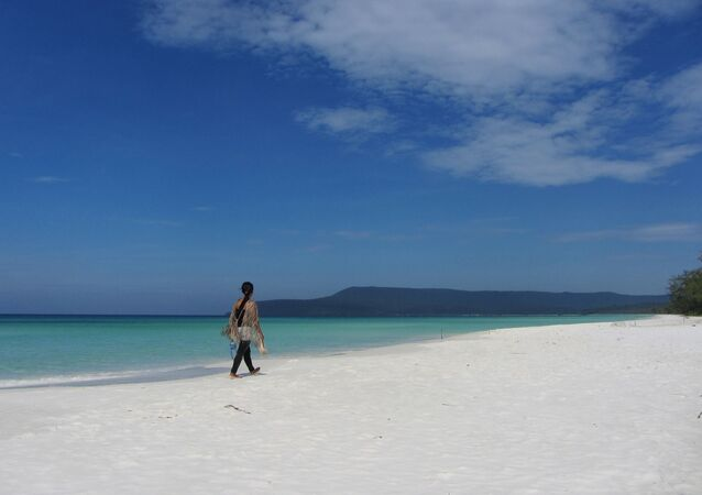 A woman walks along the beach in Koh Rong, Cambodia
