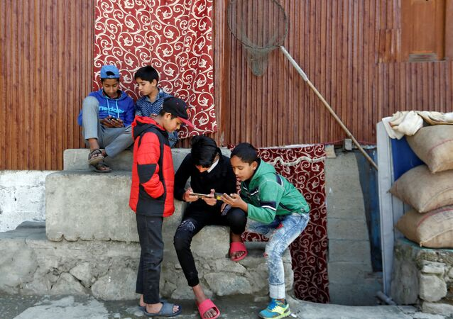 Children play games on their mobile phones in a neighbourhood in Srinagar October 10, 2019