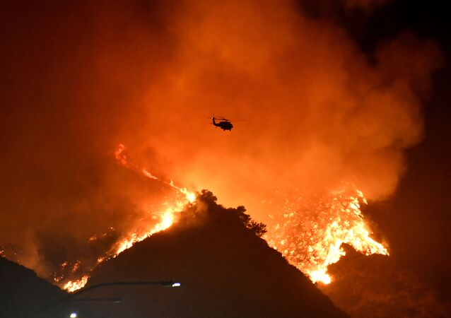 A firefighting helicopter flies over the Getty Fire as it burns in the hills west of the 405 freeway in the hills of West Los Angeles, California, U.S. October 28, 2019