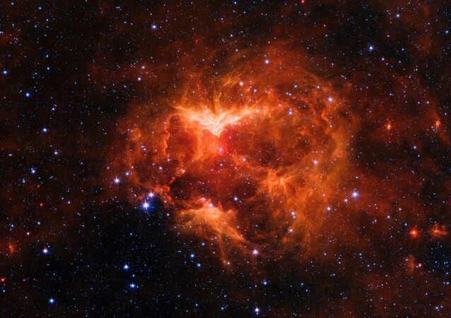 This infrared image from NASA's Spitzer Space telescope shows a cloud of gas and dust carved out by a massive star. A drawing overlaid on the image reveals why researchers nicknamed this region the Jack-o'-lantern Nebula.
