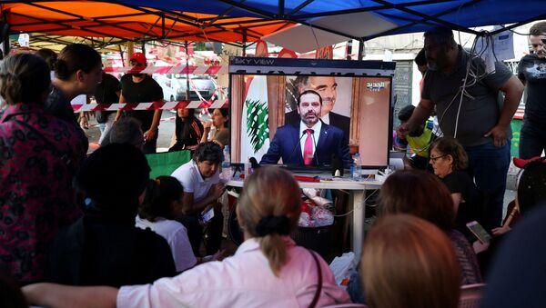 Protestors watch a television broadcast of Lebanon's Prime Minister Saad al-Hariri speaking, in Sidon, Lebanon - Sputnik International