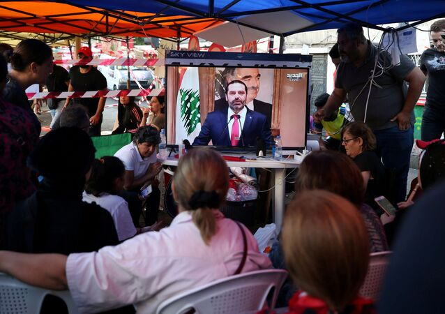 Protestors watch a television broadcast of Lebanon's Prime Minister Saad al-Hariri speaking, in Sidon, Lebanon