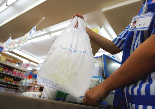A store clerk hands a plastic bag of goods at a pay counter at a convenience store in Tokyo Thursday, June 8, 2006. Facing criticism from environmentalists, Japan is now trying to cut back on plastic waste with a new law that gives the government the right to warn and give corrective orders to retailers that don't make enough efforts to save on plastic.