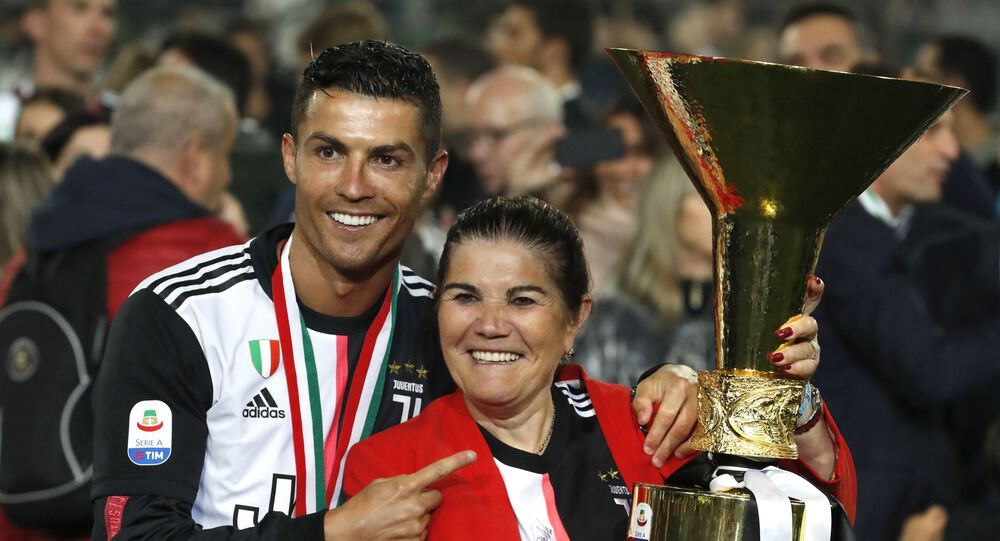 Juventus' Cristiano Ronaldo poses with his mother Dolores Aveiro, right, after winning the Serie A soccer title trophy, at the Allianz Stadium, in Turin, Italy, Sunday, May 19, 2019.