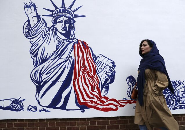 A woman walks past a satirical drawing of the Statue of Liberty after new anti-US murals on the walls of former US embassy were unveiled in a ceremony in Tehran, Iran, 2 November 2019.