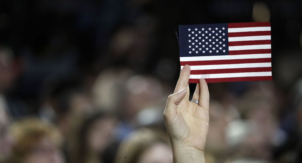 A small American flag is held aloft during Democratic presidential nominee Hillary Clinton's election night rally in the Jacob Javits Center glass enclosed lobby in New York, Tuesday, Nov. 8, 2016.