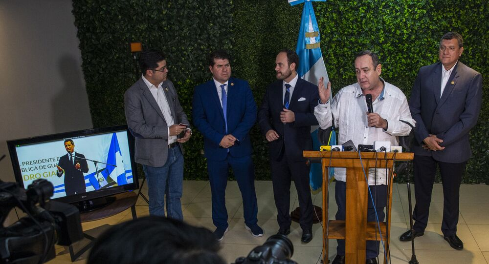 Guatemala's President-elect Alejandro Giammattei, second from right, talks with reporters as National Assembly President and self-proclaimed interim president of Venezuela Juan Guaido is seen on a screen
