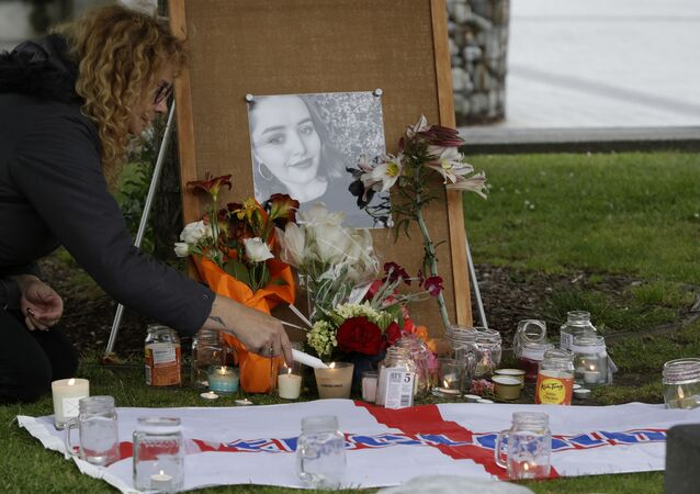 A woman lights candles during a vigil for murdered British tourist Grace Millane in Christchurch, New Zealand