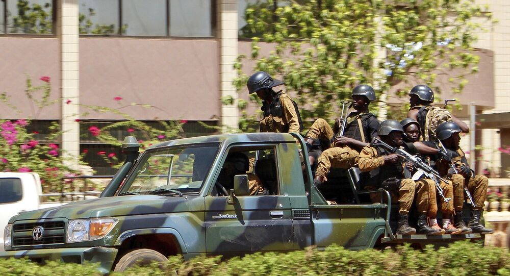 Troops ride in a vehicle near the French Embassy in central Ouagadougou, Burkina Faso