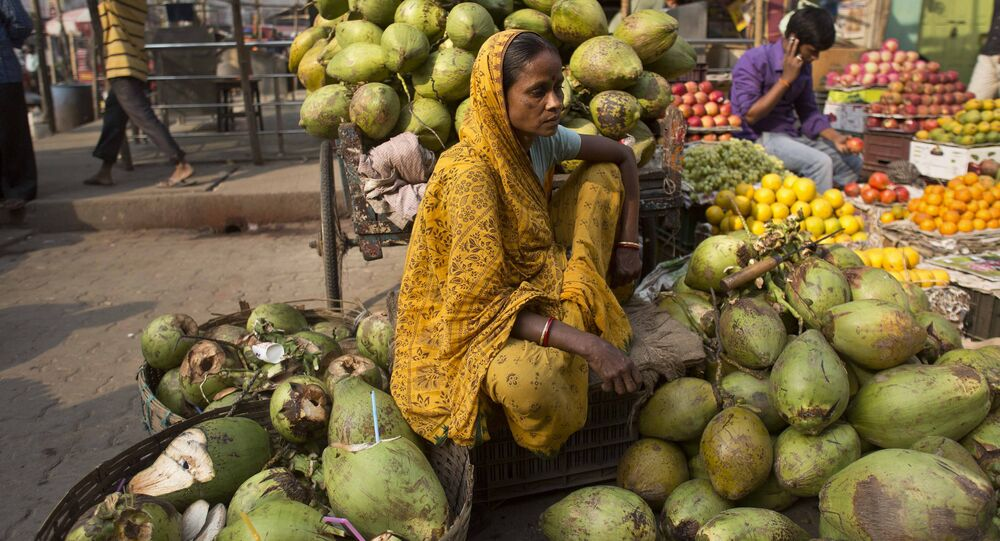 An Indian woman waits for customers as she sells coconuts at a market in Gauhati, India, 12 April 2017.