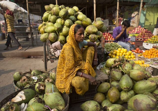 An Indian woman waits for customers as she sells coconuts at a market in Gauhati, India, Wednesday, April 12, 2017.