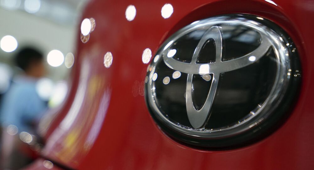 FILE - In this Aug. 2, 2019, file, photo, people walk by the logo of Toyota at a show room in Tokyo