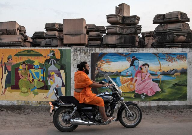 A Hindu priest rides past a workshop where the pillars that Hindu nationalist group Vishva Hindu Parishad (VHP) say will be used to build a Ram temple at the disputed religious site are kept, in Ayodhya, India, October 22, 2019