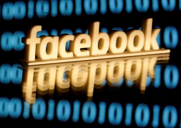 A 3-D printed Facebook logo is seen in front of displayed binary code in this illustration picture, June 18, 2019