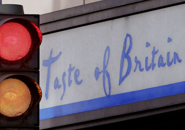 Traffic lights shine red and orange in front of a small shop that offers British specialities