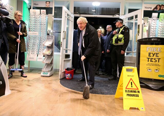 Britain's Prime Minister Boris Johnson mops the floor to help with the clean-up at an opticians during a visit to the flood-hit town of Matlock, Derbyshire, Britain November 8, 2019. Picture taken November 8, 2019. Danny Lawson